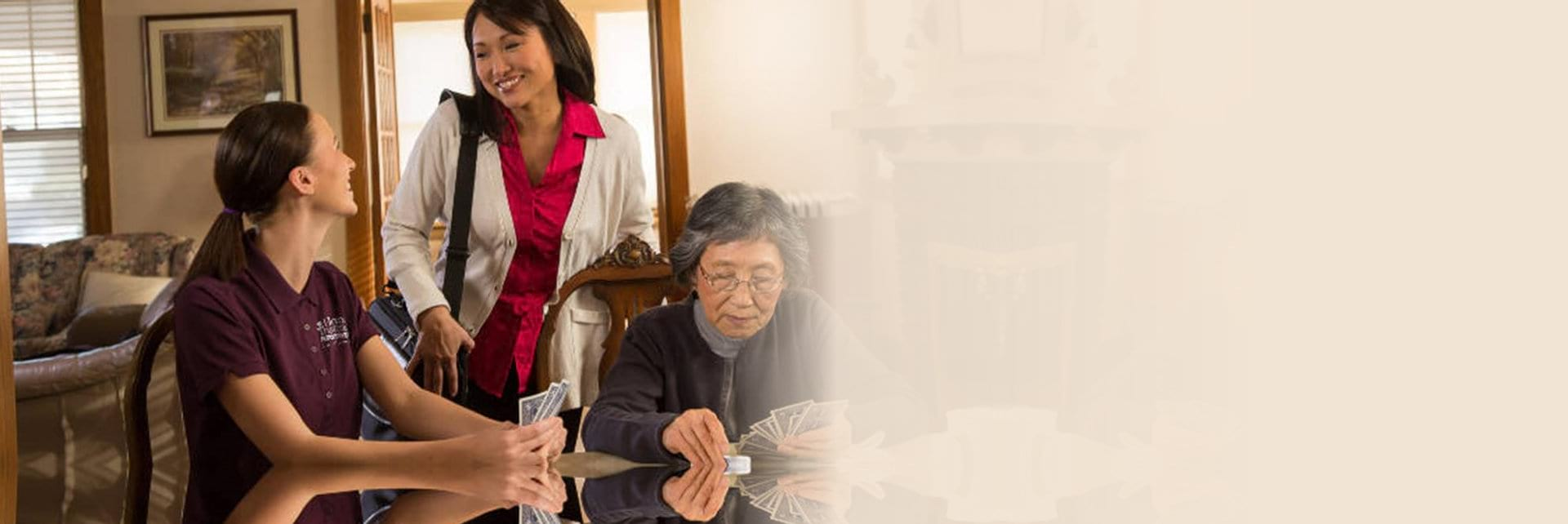 Elder woman playing cards and two women talking