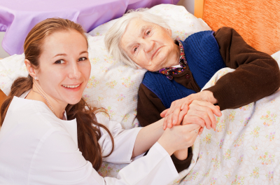Caregiver and an elder woman on the bed