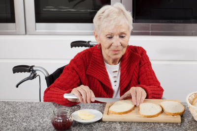 Disabled older woman preparing sandwiches for breakfast