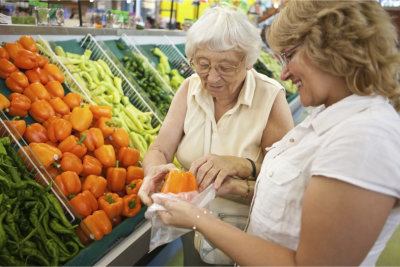 Caregiver and an elder woman buying fruits