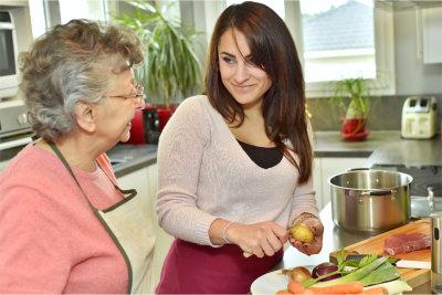 Caregiver helping the elder woman preparing meal