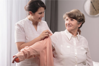 Caregiver assisting the elder woman in dressing