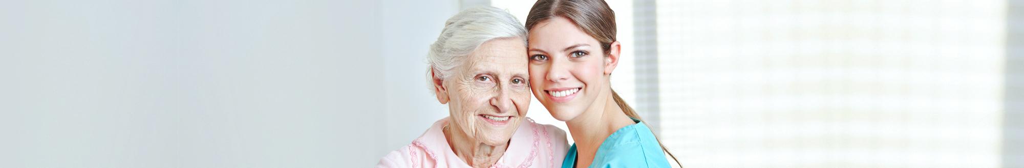Caregiver embracing happy senior