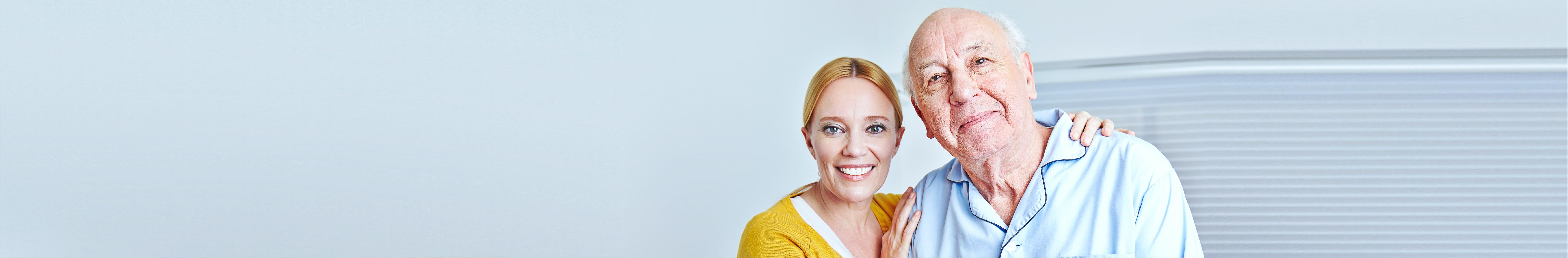 Smiling caregiver nursing senior men in family at home