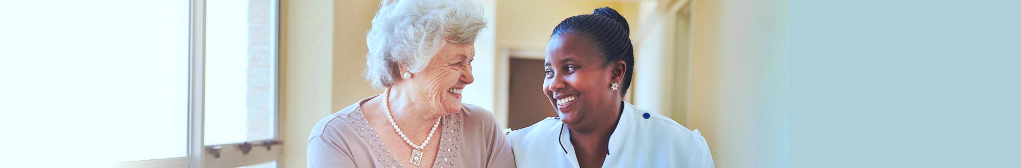 Portrait of smiling home caregiver and senior women walking together